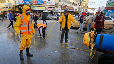 Municipality workers wearing protective clothes disinfect a street in Khan Younis in the southern Gaza Strip as part of measures to prevent the spread of the coronavirus, March 14, 2020. Photo by Abed Rahim Khatib/Flash90.