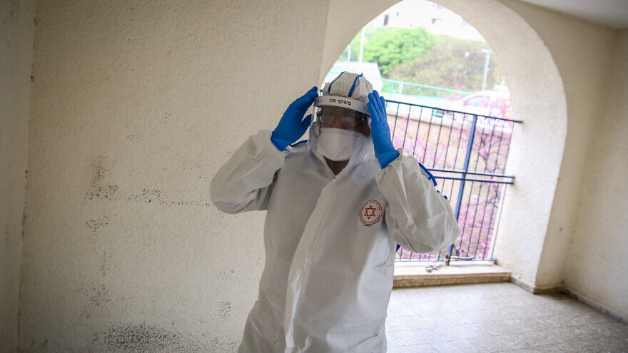 A Magen David Adom worker wearing protective clothing as a preventive measure against the coronavirus arrives to test a patient with symptoms of the coronavirus) in the northern Israeli city of Tzfat, March 17, 2020. Photo by David Cohen/Flash90.