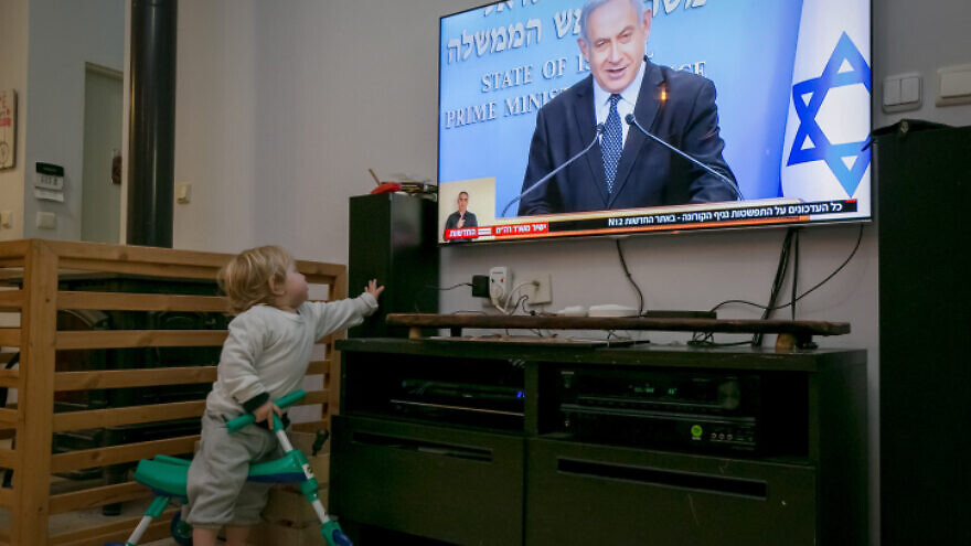 A child watches as Israeli Prime Minister Benjamin Netanyahu holds a live press conference on the new government restrictions for the public regarding the COVID-19 crisis on March 19, 2020. Photo by Chen Leopold/Flash90.
