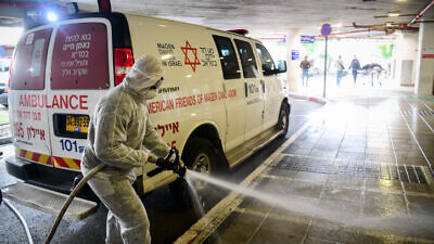 Israeli firefighters wear protective clothes to disinfect Ichilov Hospital in Tel Aviv as part of measures to prevent the spread of the coronavirus, March 20, 2020. Photo by Flash90.