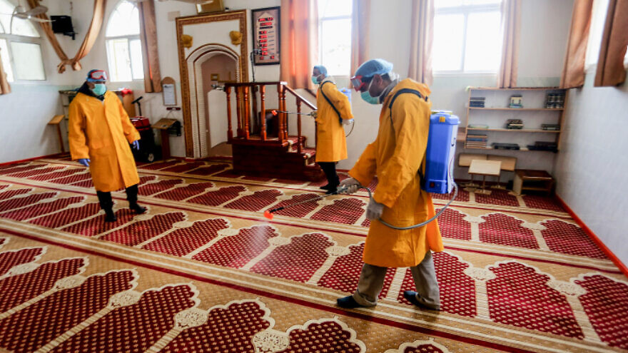 Palestinian health workers spray disinfectant in a mosque as a precaution against COVID in Rafah, in the southern Gaza Strip, on March 22, 2020. Photo by Abed Rahim Khatib/ Flash90.