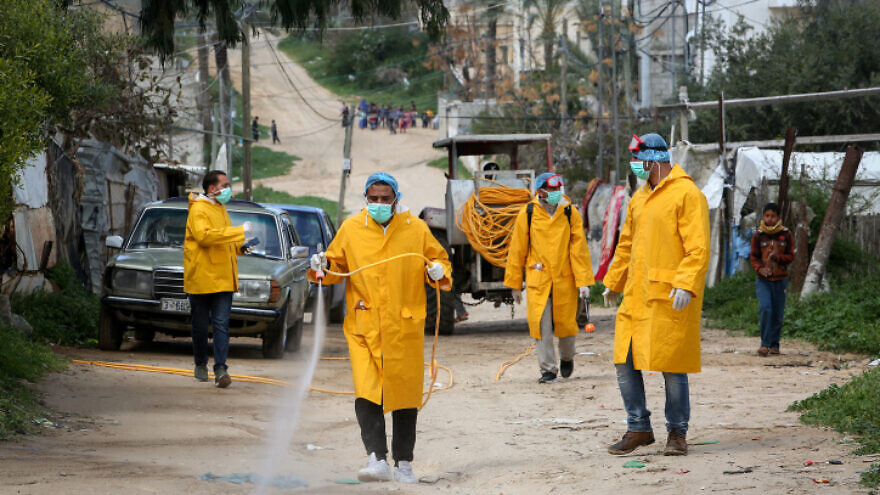 Palestinian health workers spray disinfectant as a precaution against the spread of the COVID-19 virus, in Rafah, southern Gaza Strip, on March 22, 2020. Photo by Abed Rahim Khatib/ Flash90.