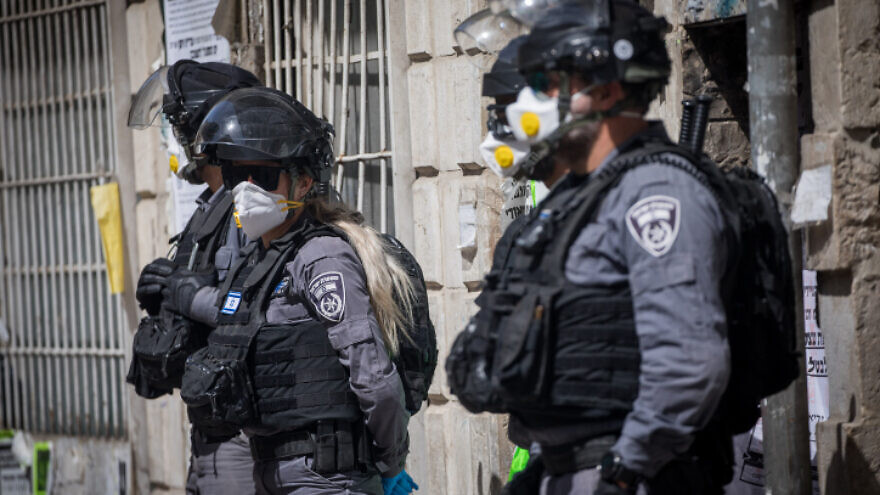 Israeli police officers enter the ultra-Orthodox Jewish neighborhood of Me'a Shearim in Jerusalem, closing shops and dispersing public gatherings as part of the country's efforts to stem the spread of the coronavirus pandemic, March 24, 2020. Photo by Yonatan Sindel/Flash90.