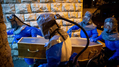 Chevra Kadisha workers wearing protective suits at the Shamgar Funeral Home in Jerusalem carry the body of a man who died of COVID-19 complications, March 24, 2020. Photo by Yonatan Sindel/Flash90.