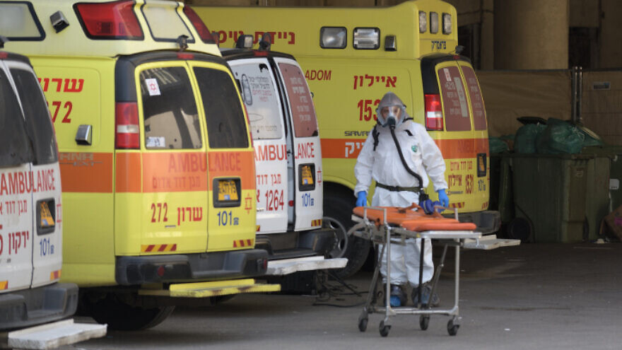 An Israeli medical team member clean and disinfect an ambulance at Tel Aviv's Dan Panorama hotel, which was turned into quarantine facility for coronavirys patients, on March 26, 2020. Photo by Gili Yaari/Flash90.