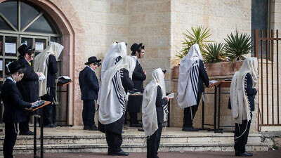 Jewish men pray outside a synagogue in the city of Beitar Illit in Judea and Samaria, on March 29, 2020. Photo by Aharon Krohn/Flash90.