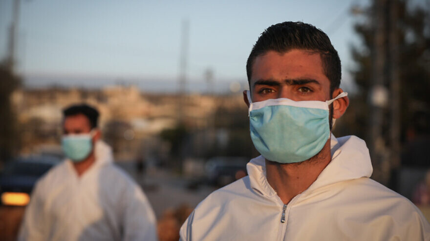 Palestinian medical employees disinfect Palestinian workers returning from their jobs in Israel at the entrance to the West Bank village of Hussan, on March 29, 2020. Photo by Nati Shohat/Flash90.