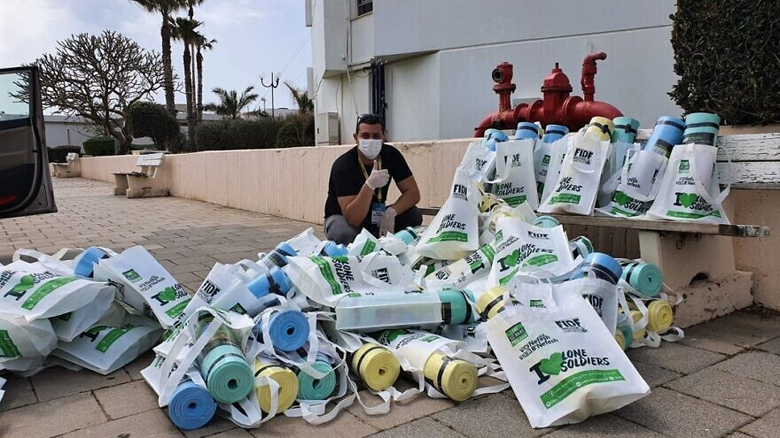 An Israeli solder organizes a delivery of yoga mats from Friends of the IDF to an Israel Defense Forces base, March 24, 2020. Courtesy: FIDF.