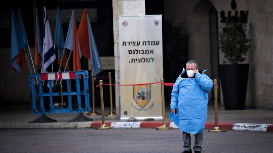 An Israeli worker stands outside the Dan Hotel in Jerusalem that was converted to receive coronavirus patients, March 19, 2020. Photo by Yonatan Sindel/Flash90.