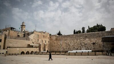 A religious Jew walks near the Western Wall in the Old City of Jerusalem on March 27, 2020. The government ordered a partial lockdown to prevent the spread of the coronavirus (COVID-19). Photo by Yonatan Sindel/Flash90.