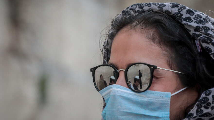 A woman wears face mask to protect herself against the coronavirus (COVID-19) as she attends a bar mitzvah, at the Western Wall in Jerusalem's Old City on March 19, 2020. Photo by Yossi Zamir/Flash90.