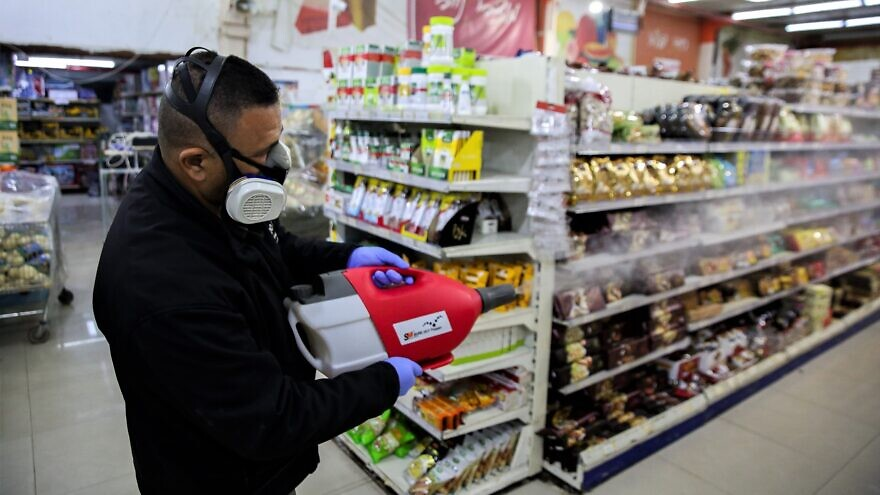 Workers disinfect Bar Kol Supermarket in the northern Israeli city of Tzfat as part of measures to prevent the spread of the coronavirus, March 16, 2020. Photo by David Cohen/Flash90.