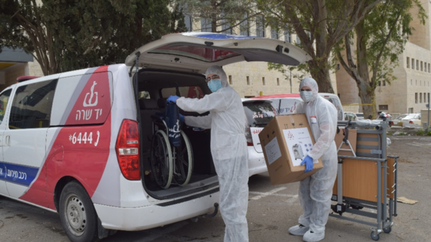 Yad Sarah volunteers in protective gear distribute medical equipment to individuals under mandatory 14-day quarantine in Israel due to possible coronavirus infection, on March 10, 2020. Credit: Yad Sarah.
