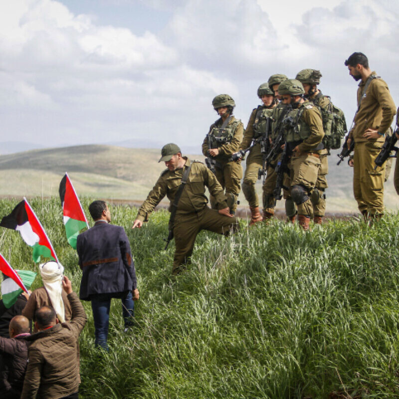 Israeli troops look on as Palestinian demonstrators protest against U.S. President Donald Trump's Middle East peace plan, near the town of Beqa'ot in the Jordan Valley, Feb. 29, 2020. Photo by Nasser Ishtayeh/Flash90.