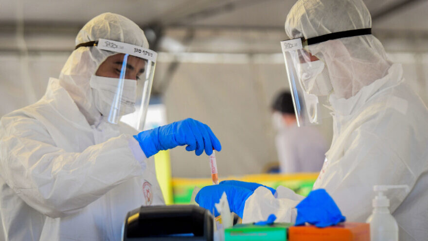 Magen David Adom medical team members handle a coronavirus test sample at a drive-through testing site in Tel Aviv on March 22, 2020. Photo by Flash90.