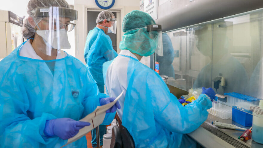 Technicians carry out a diagnostic test for COVID-19 in a lab at the Rambam Health Care Campus in Haifa, on March 30, 2020. Photo by Yossi Aloni/Flash90.