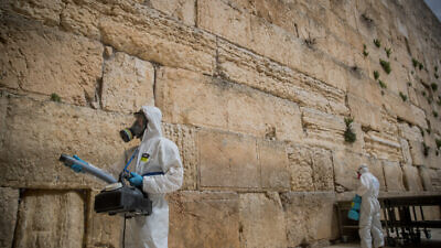 Israeli workers disinfect the Western Wall in the Old City of Jerusalem as a preventive measure against the spread of the COVID-19 virus, March 31, 2020. Photo by Yonatan Sindel/Flash90.