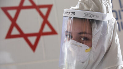 A medical team worker wears protective clothing outside the new coronavirus unit at the Shaare Zedek Medical Center in Jerusalem on April 2, 2020. Photo by Nati Shohat/Flash90.