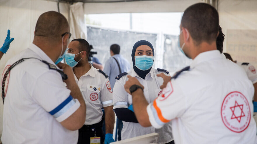 Magen David Adom medical workers collect samples for coronavirus testing at a drive-through testing site at the entrance to the eastern Jerusalem village of Jabel Mukaber on April 2, 2020. Photo by Yonatan Sindel/Flash90.
