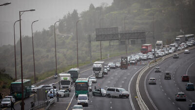 Israeli police officers pull over a bus on Highway 1 near Jerusalem to arrest a man that earlier tested positive for coronavirus, on April 5, 2020. Photo by Yonatan Sindel/Flash90.