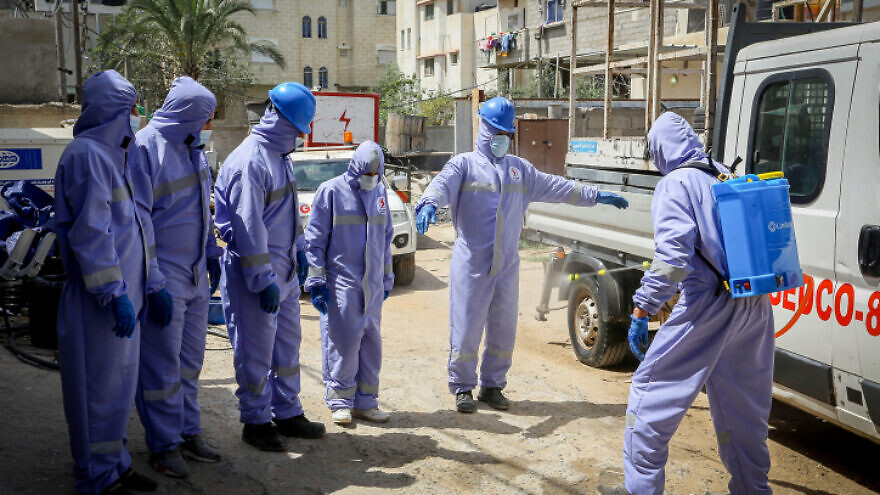 Palestinian Energy Company workers wear protective clothing and masks during their work following the outbreak of the coronavirus (COVID-19) in the Gaza Strip, April 6, 2020. Photo by Abed Rahim Khatib/Flash90.