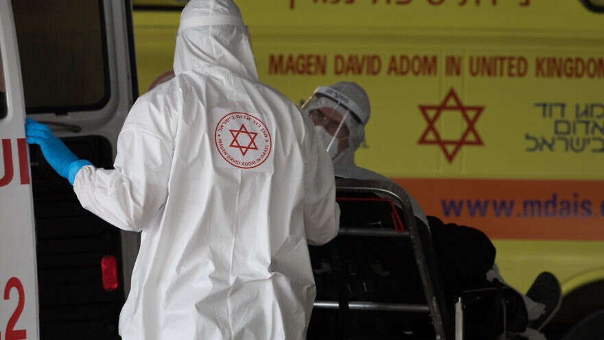 Magen David Adom workers wearing protective clothing as a preventive measure against the coronavirus evacuate a patient outside the new coronavirus unit at Shaare Zedek Medical Center in Jerusalem on April 6, 2020. Photo by Nati Shohat/Flash90.
