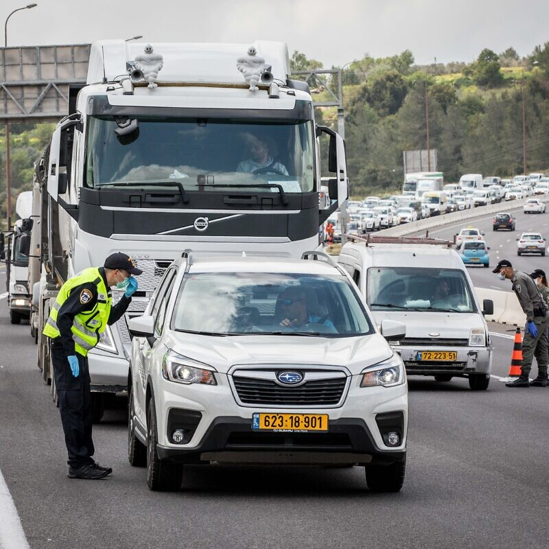"Police check drivers at a temporary ""checkpoint"" on road number 1 outside Jerusalem, to check if people are not disobeying the governments orders on a partial lockdown, in order to prevent the spread of the Coronavirus. Photo by Nati Shohat/Flash90"