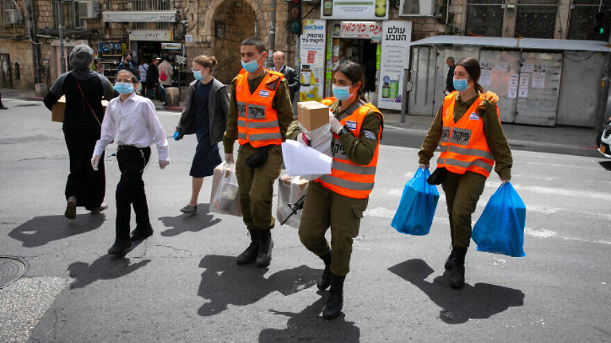 Israeli soldiers in the Home Front Command Unit give out food packages to elderly people in Jerusalem obliged to stay home due to the coronavirus pandemic, April 7, 2020. Photo by Olivier Fitoussi/Flash90.