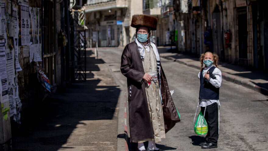 An ultra-Orthodox man and his son shop for goods in the Mea Shearim neighborhood of Jerusalem on April 12, 2020. Photo by Yonatan Sindel/Flash90.