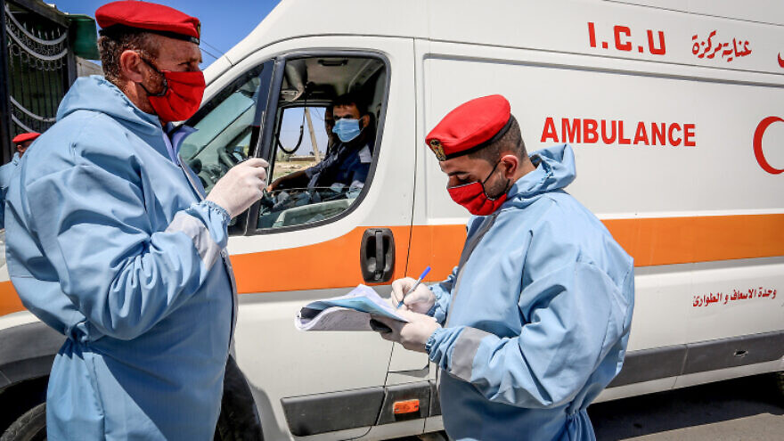 Security forces loyal to Hamas check the papers of an intensive-care ambulance during the coronvirus pandemic at the Rafah border crossing with Egypt in the southern Gaza Strip, April 13, 2020. Photo by Abed Rahim Khatib/Flash90.