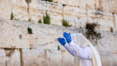 A man prays at the Western Wall in Jerusalem's Old City during the Jewish holiday of Passover, April 13, 2020. Photo by Olivier Fitoussi/Flash90.