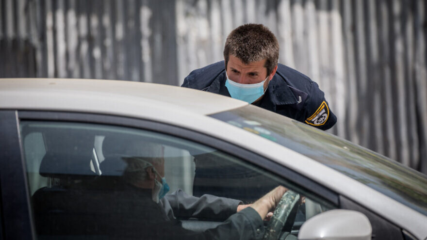 An Israeli police officer questions drivers at a temporary checkpoint in Jerusalem on April 19, 2020. Photo by Yonatan Sindel/Flash90.