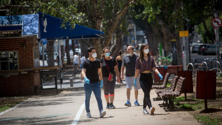 Pedestrians in Israel wear face masks, which are mandated by the Health Ministry as a preventative measure against the spread of coronavirus (COVID-19), on Rothschild Boulevard in Tel Aviv, April 22, 2020. Photo by Miriam Alster/Flash90.
