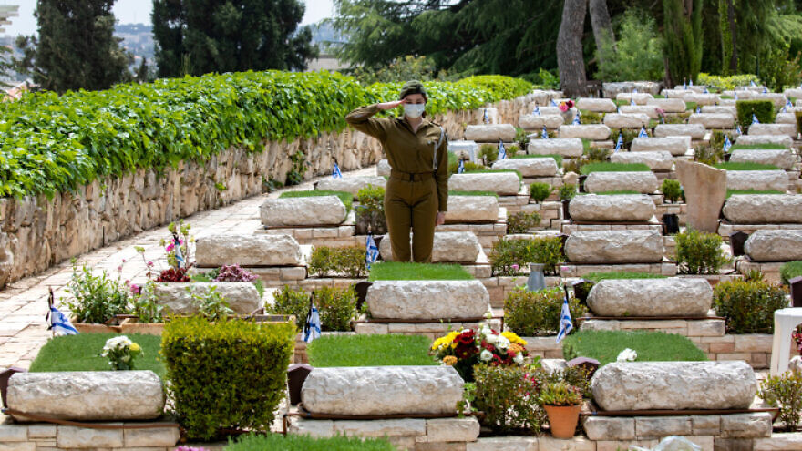 An Israeli soldier salutes at the Mount Herzl Military Cemetery in Jerusalem, on the eve of Israel's Memorial Day, April 26, 2020. Photo by Olivier Fitoussi/Flash90.