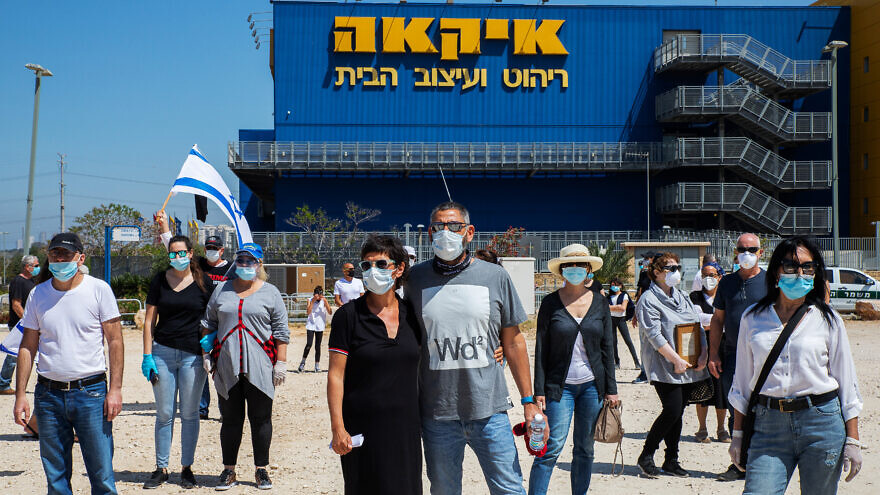 Families, friends and comrades of fallen soldiers and terror victims hold a Memorial Day ceremony outside the Ikea store in Rishon Letzion as part of a protest against the government's closure of military cemeteries on Memorial Day, April 28, 2020. Photo by Cadya Levy/Flash90.