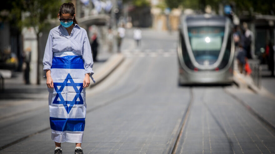 Pedestrians and drivers stand still as a siren sounds across Israel to mark Yom Hazikaron, the country's Memorial Day, which commemorates fallen Israeli soldiers and victims of terror, in Jerusalem on April 28, 2020. Photo by Yonatan Sindel/Flash90.