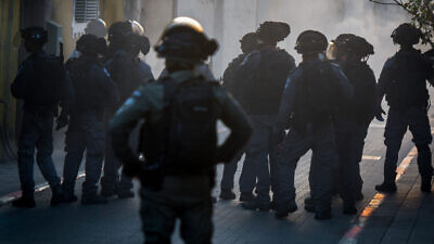 Israel Police officers stand guard during clashes with residents in Jaffa following the arrest of a resident who violated his home quarantine, April 1, 2020. Photo by Avshalom Sassoni/Flash90.