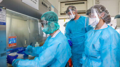 Technicians carry out a diagnostic test for the coronavirus in a lab at the Rambam Health Care Campus in Haifa on March 30, 2020. Photo by Yossi Aloni/Flash90.