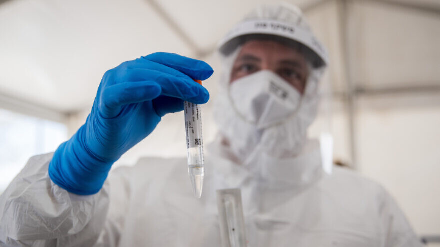 A Magen David Adom medical worker conducts coronavirus tests at the entrance to the easterm Jerusalem village of Jabel Mukaber, on April 2, 2020. Photo by Yonatan Sindel/Flash90.
