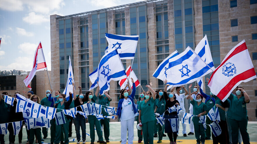 Hadassah Ein Kerem Medical team cheer an Israeli airforce acrobatic team flies over Hadassah Ein Kerem hospital in Jerusalem on Israel's 72nd Inependence Day on April 29, 2020. Photo by Yonatan Sindel/Flash90
