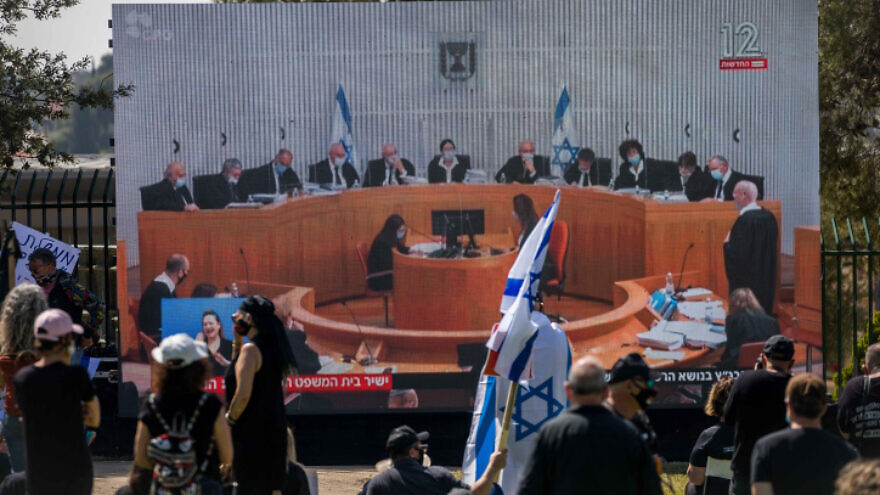 Israelis watch a Supreme Court session on petitions filed against the proposed unity government, outside the Knesset in Jerusalem, on April 3, 2020. Photo by Yonatan Sindel/Flash90.