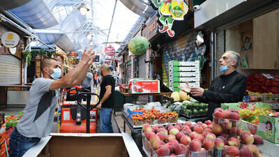 Shoppers at the Machane Yehuda market in Jerusalem after it reopened on May 7, 2020, following weeks of COVID-19 lockdowns. Photo by Olivier Fitoussi/Flash90.