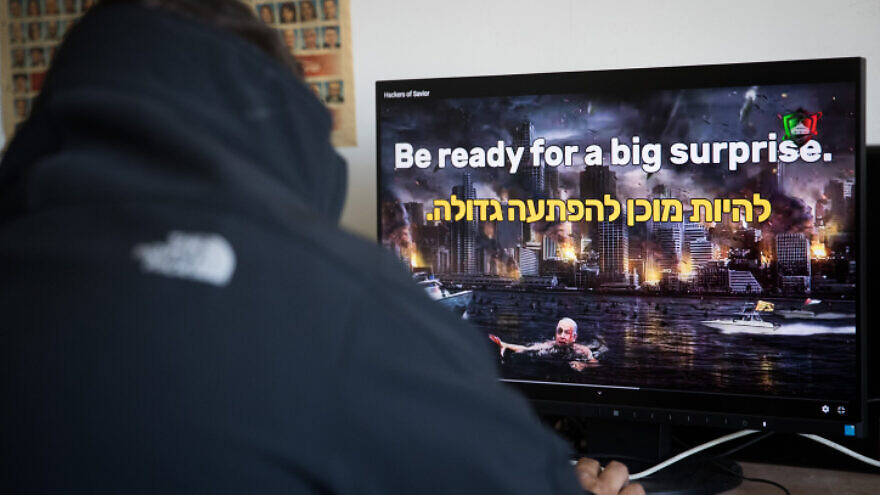 "A man watches a video on an Israeli website hacked by a group calling itself the ""Hacking Saviours"" in an office in Jerusalem on May 21, 2020. Photo by Yonatan Sindel/Flash90."
