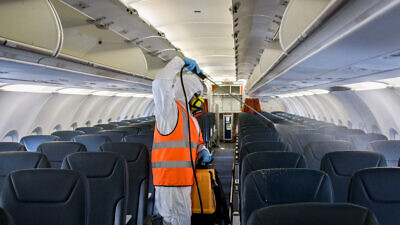 A worker wearing protective clothing disinfects a plane after its arrival from Moscow at the Ben-Gurion International Airport as part of measures to prevent the spread of the coronavirus, May 5, 2020. Photo by Yossi Zeliger/Flash90.
