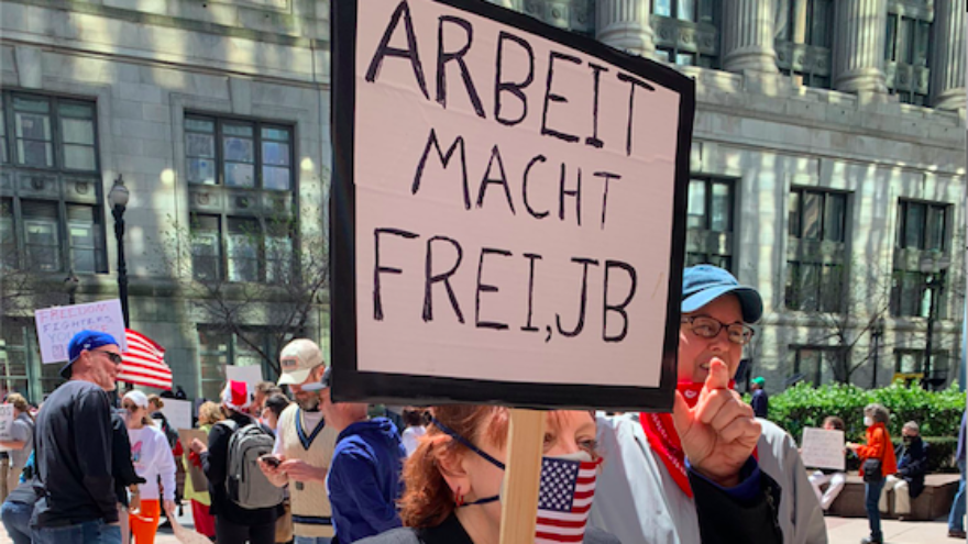 """A sign with the Nazi slogan """"works sets you free,"""" addressed to Illinois Gov. J.B. Pritzker, appears at a protest in Chicago over coronavirus restrictions. Source: Screenshot via Dennis Kosuth."""