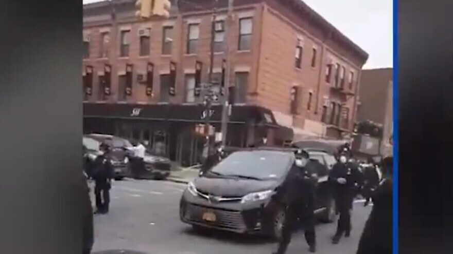 A view of New York City police officers dispersing a crowded funeral procession for a Chassidic rabbi and Holocaust survivor in the Borough Park neighborhood of Brooklyn, N.Y., on April 30, 2020. Source: Screenshot.