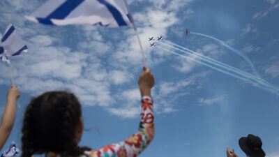 People at Bugrashov Beach in Tel Aviv watch the military airshow on Israel's 71st Independence Day, May 9, 2019. Photo by Hadas Parush/Flash90.
