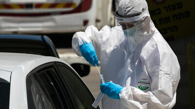Magen David Adom medical workers test Israelis at a drive-through coronavirus testing site in Jerusalem on May 31, 2020. Photo by Olivier Fitoussi/Flash90.