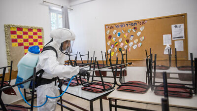 Workers disinfect a classroom at the Gymnasia Rehavia high school in Jerusalem on June 3, 2020. Photo by Yonatan Sindel/Flash90.