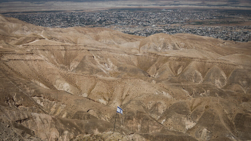 An Israeli flag with a view of the Jordan Valley on June 14, 2020. Photo by Yonatan Sindel/Flash90.